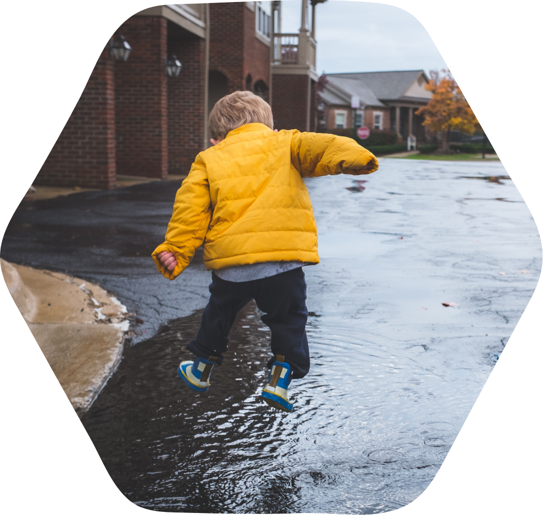 A kid jumping in a puddle