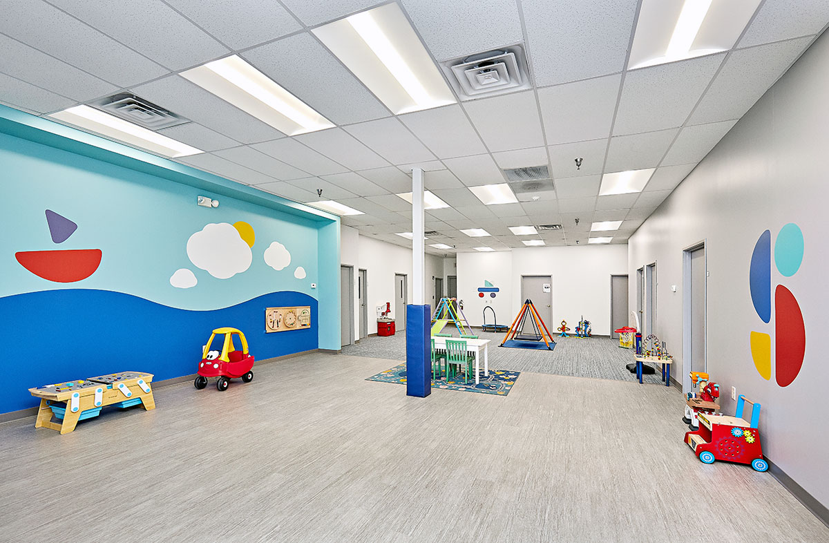 View of interior open space with toys, a table, and multiple doors at the Stride Autism Center in Clive, Iowa
