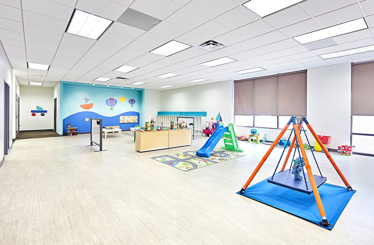 View of interior open space with toys, a table, and multiple doors at the Stride Autism Center in Davenport, Iowa.